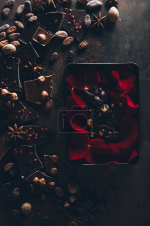 Photo for Top view of red rose petals in box with delicious chocolate pieces, nuts and cocoa beans on dark surface - Royalty Free Image