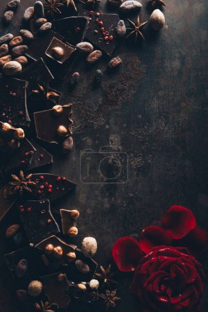 Photo for Top view of chocolate pieces with cocoa beans, nuts, star anise and rose petals on dark surface - Royalty Free Image