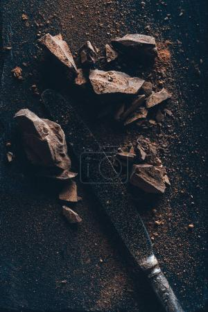 Photo for Top view of vintage knife, chocolate pieces and cocoa powder on dark surface - Royalty Free Image