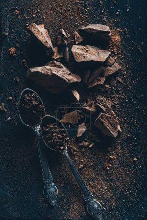 Ansicht von Vintage-Löffeln, Schokoladenstücken und Kakaopulver auf dunkler Oberfläche