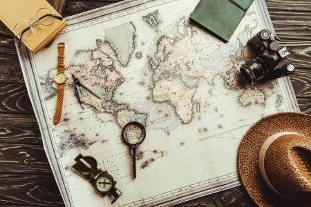 Photo for Flat lay with straw hat, map, magnifying glass, compass and retro photo camera on dark wooden tabletop - Royalty Free Image