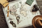 flat lay with straw hat, map, magnifying glass, compass and retro photo camera on dark wooden tabletop