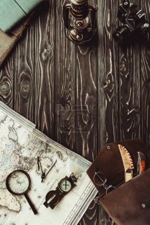 Photo pour Vue de dessus de l'arrangement avec carte, loupe, sac, boussole et appareil photo rétro sur surface en bois sombre - image libre de droit