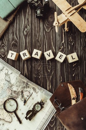 top view of arranged wooden blocks in travel word with map, retro photo camera, bag and magnifying glass on dark wooden tabletop