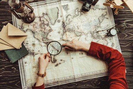 Teilbild einer Frau mit Lupe auf der Suche nach dem Reiseziel auf einer Holztischplatte mit Fotokamera, Kompass und Umschlägen