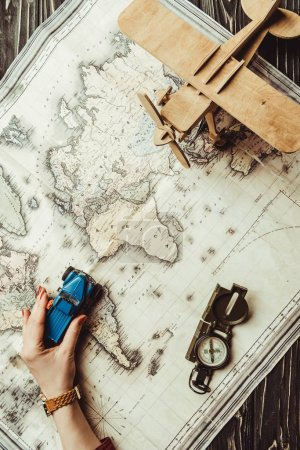 Photo for Partial view of female hand with toy car, compass, wooden toy plane and map on wooden surface - Royalty Free Image
