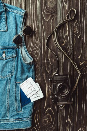 flat lay with denim vest, passports, tickets, sunglasses and retro photo camera on dark wooden surface