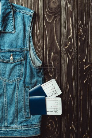 flat lay with denim vest, passports and tickets on dark wooden surface