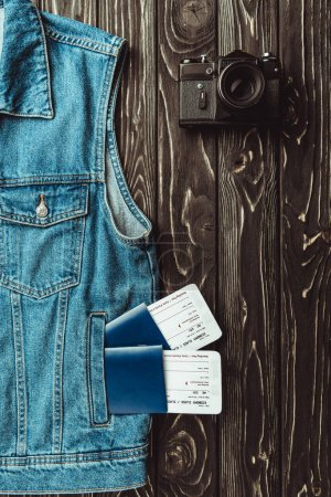 flat lay with denim vest, passports, tickets and retro photo camera on dark wooden surface