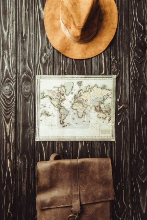 top view of arranged hat, map and bag on dark wooden surface