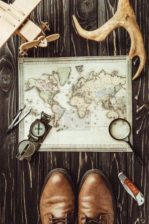 Photo pour Vue de dessus du cadre de voyage avec carte, chaussures, boussole, loupe et cornes décoratives sur une surface en bois sombre - image libre de droit