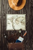 top view of travel setting with hat, map, bag with eyeglasses, compass, passport and ticket on dark wooden surface