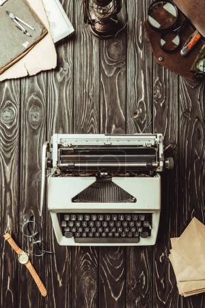 flat lay with typing machine, envelopes, eyeglasses, bag with magnifying glasses and pocket knife on dark wooden surface