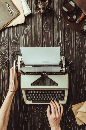 partial view of writer hands, typing machine and envelopes on wooden tabletop