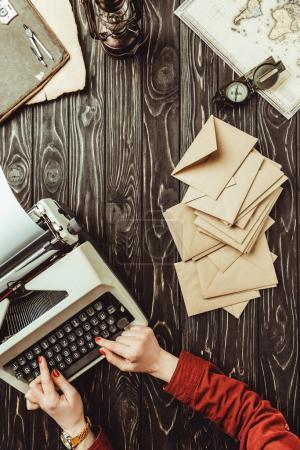 Photo pour Vue partielle de l'écrivain dactylographiant sur la machine à dactylographier avec des enveloppes vierges sur la table en bois - image libre de droit