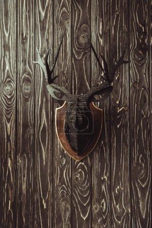 Photo pour Bouchent la vue de la tête de cerf en bois décoratif sur une surface en bois sombre - image libre de droit