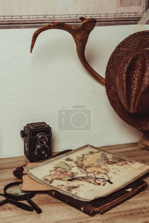 close up view of table with map, eyeglasses, magnifying glasses, retro photo camera and decorative horns