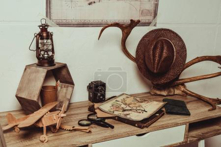 Photo for Close up view of table with map, eyeglasses, magnifying glasses, retro photo camera and decorative horns - Royalty Free Image
