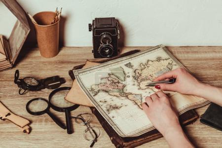 cropped shot of woman at table with map, magnifying glasses, eyeglasses and retro photo camera