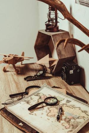 close up view of table with map, magnifying glasses and retro photo camera