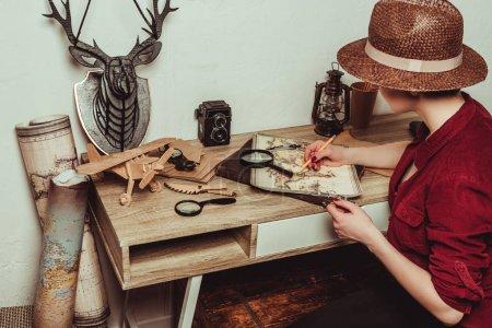 Photo pour Chapeau femme style rétro avec loupe à la recherche d'une destination sur la carte - image libre de droit