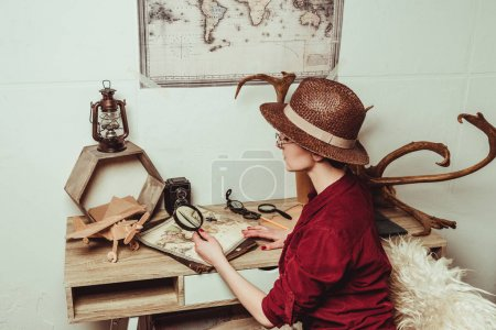 Photo for Retro style woman in hat with magnifying glass sitting at table with map - Royalty Free Image