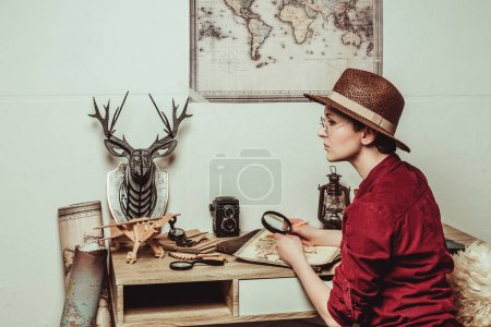 pensive retro style woman in hat with magnifying glass sitting at table with map