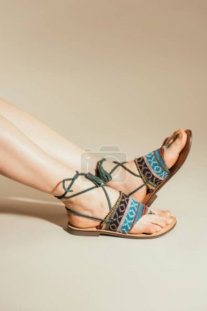 cropped shot of woman feet in stylish sandals on beige background
