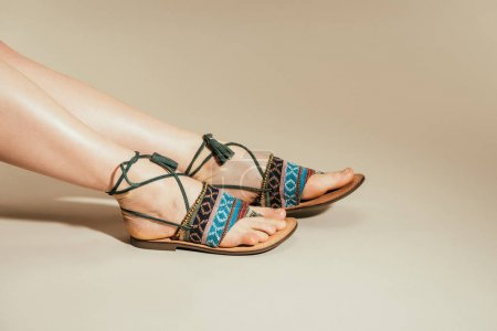 cropped image of woman feet in stylish sandals on beige background