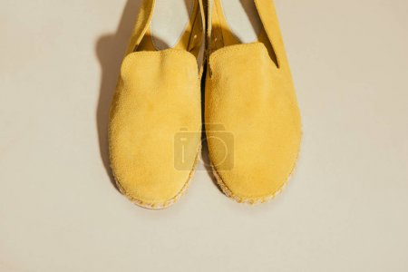 closeup view of yellow stylish espadrilles on beige background