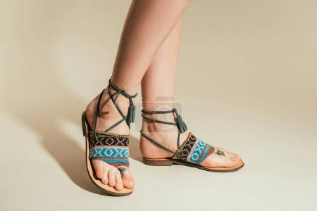 cropped shot of woman legs in stylish sandals on beige background