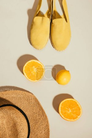 top view of straw hat, lemon, orange slices and yellow stylish espadrilles