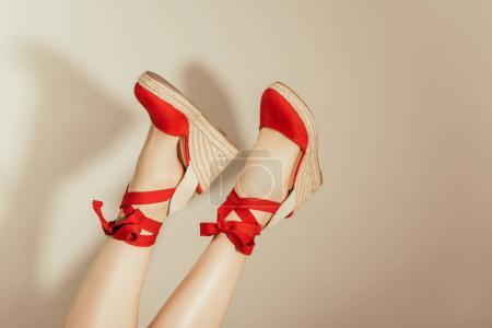 cropped shot of upside down female feet in red platform sandals on beige background