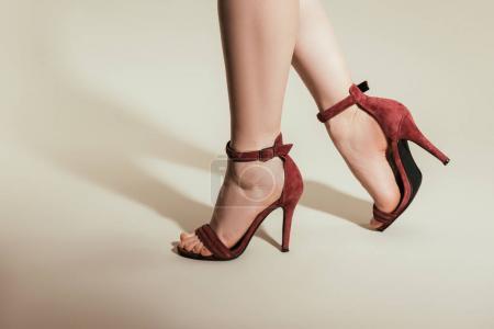 Photo pour Plan recadré de femmes pieds dans des sandales à talons hauts élégantes sur fond blanc - image libre de droit
