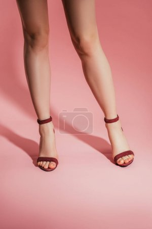 cropped shot of woman legs in stylish high heeled sandals on pink background