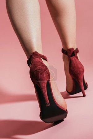 Photo pour Faible angle vue de femme pieds dans des sandales talons hauts élégants sur fond rose - image libre de droit