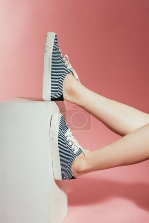Photo for Cropped shot of woman legs in stylish sneakers on pink background - Royalty Free Image