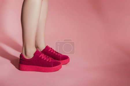 Photo for Cropped image of woman legs in stylish sneakers on pink background - Royalty Free Image