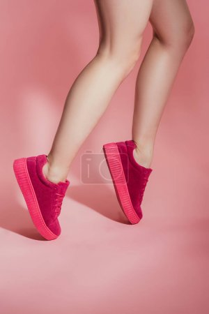 Photo for Cropped image of girl in stylish sneakers standing on toes on pink background - Royalty Free Image