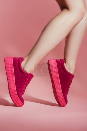 cropped shot of girl in stylish sneakers standing on toes on pink background