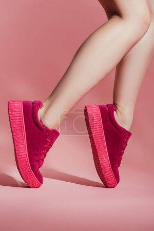 Photo pour Plan recadré de fille en baskets élégantes debout sur les orteils sur fond rose - image libre de droit