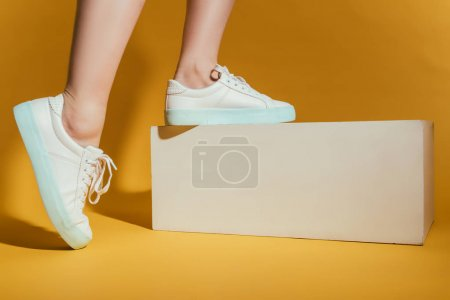 cropped image of woman feet in stylish sneakers on yellow background