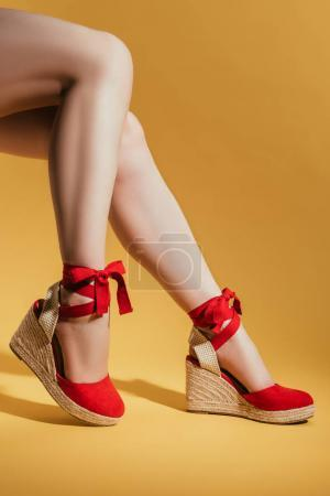 cropped shot of woman legs in stylish platform sandals on yellow background