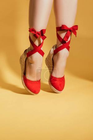 Photo pour Image recadrée de la femme dans des sandales plates-formes élégantes debout sur les orteils sur fond jaune - image libre de droit