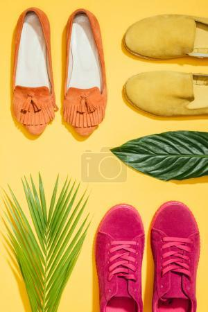 top view of tropical leaves and stylish female shoes on yellow background