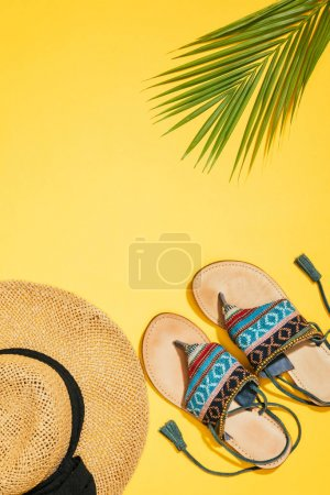 elevated view of straw hat, palm leaf and stylish female sandals on yellow background