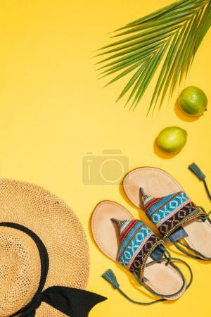 top view of two limes, palm leaf, blue stylish sandals and straw hat on yellow background