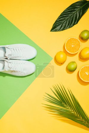 top view of stylish female sneakers, tropical leaves, lemons, limes and slices of orange