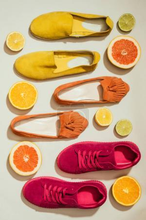 Photo for Top view of stylish female shoes placed in row surrounded by slices of different citrus fruits on white background - Royalty Free Image