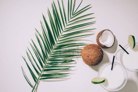 top view of glasses with coconut cocktails, lime and drinking straws, green palm leaves and exotic coconuts on white
